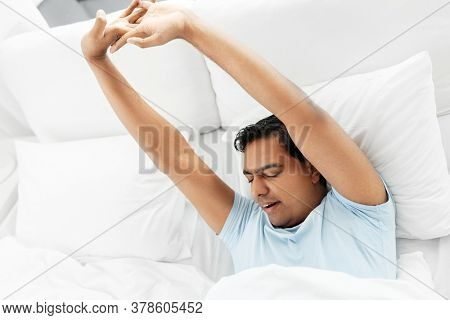 people, bedtime and rest concept - sleepy indian man stretching in bed at home
