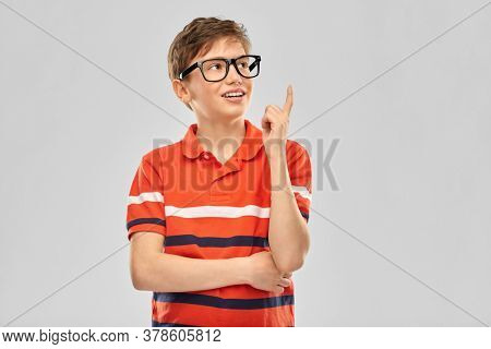 vision, education and school concept - portrait of happy smiling boy in eyeglasses and red polo t-shirt pointing finger up over grey background