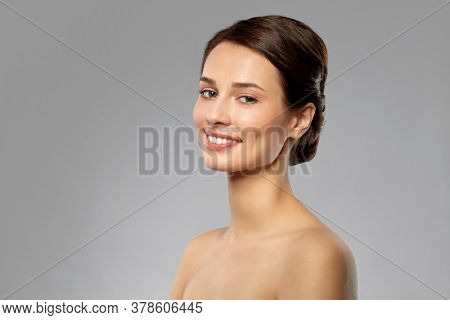 beauty, bodycare and people concept - beautiful smiling young woman with bare shoulders over grey background