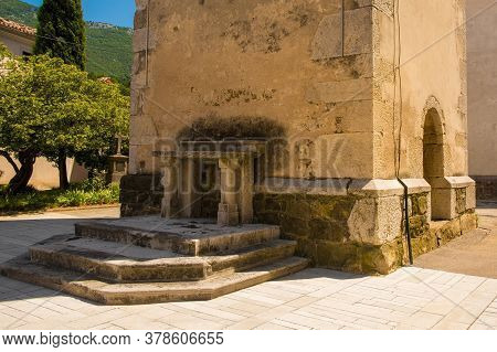 An Historic Stone Altar Next To The Bell Tower Of Saint Vitus Parish Church In Podnanos, A Village I
