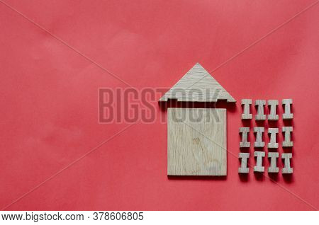 Wooden House From A Childrens Constructor On A Coral Background. Simple House Made Of Wooden Geometr