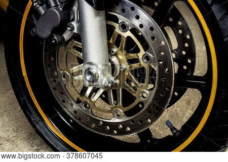 Front Wheel With Brake Discs Of A Sports Motorcycle Close-up On Concrete. Rubber With Black Alloy Di