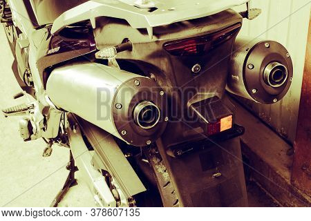 Exhaust Pipes And Brake Light Of A Motorcycle Closeup In Garage. The Noise Of A Road Bike. Wheel, Ex