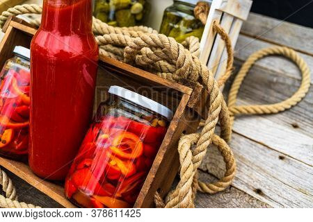 Wooden Crate With Bottles With Tomatoes Sauce And Glass Jars With Pickled Red Bell Peppers Isolated