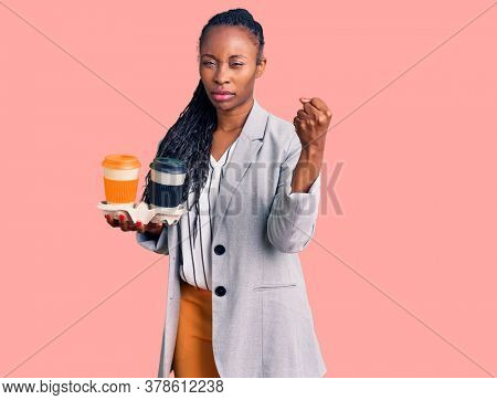 Young african american woman wearing business clothes holding take away cup of coffee annoyed and frustrated shouting with anger, yelling crazy with anger and hand raised