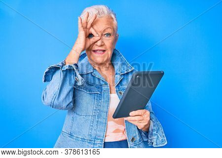 Senior beautiful woman with blue eyes and grey hair using touchpad device smiling happy doing ok sign with hand on eye looking through fingers