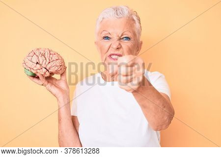 Senior beautiful woman with blue eyes and grey hair holding brain as mental health concept annoyed and frustrated shouting with anger, yelling crazy with anger and hand raised