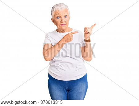 Senior beautiful woman with blue eyes and grey hair wearing casual white tshirt pointing aside worried and nervous with both hands, concerned and surprised expression