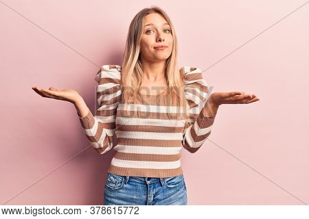 Young blonde woman wearing casual clothes clueless and confused with open arms, no idea and doubtful face.
