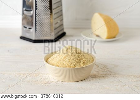 Wheat Bread Crumbs In A Beige Ceramic Bowl On A Kitchen Table. A Crust Of Dry Bread And A Grater In