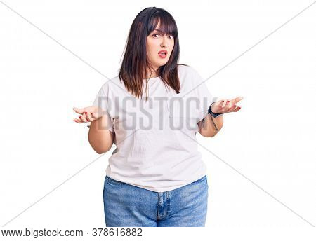 Young plus size woman wearing casual clothes clueless and confused with open arms, no idea concept.