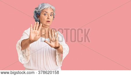 Senior woman with gray hair wearing bohemian style moving away hands palms showing refusal and denial with afraid and disgusting expression. stop and forbidden.