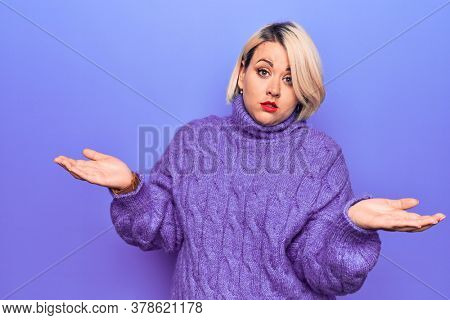 Beautiful blonde plus size woman wearing casual turtleneck sweater over purple background clueless and confused with open arms, no idea concept.