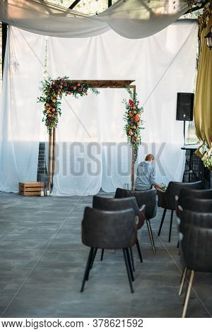 Florist Decorator At Work. Wooden Arch For The Wedding Ceremony, Decorated Cloth, Flowers And Greene