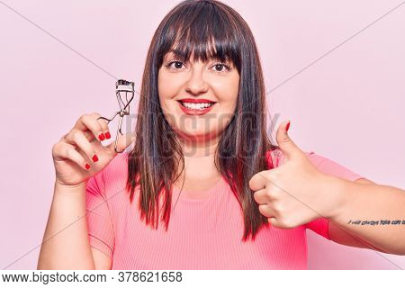 Young plus size woman holding eyelash curler smiling happy and positive, thumb up doing excellent and approval sign
