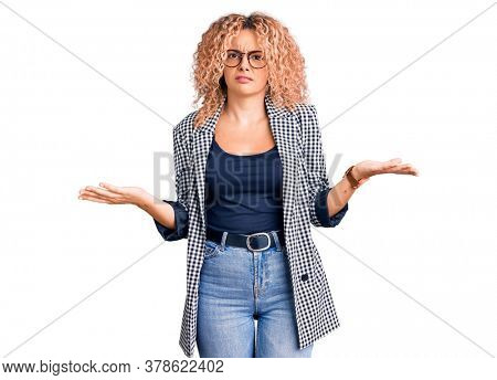 Young blonde woman with curly hair wearing business jacket and glasses clueless and confused with open arms, no idea concept.