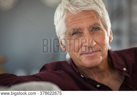 Portrait of happy senior man smiling at home. Old man relaxing on sofa and looking at camera with copy space. Close up face of elderly guy enjoying retirement.