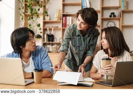 Image of multinational focused colleagues discussing project while working with laptops in office