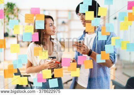 Image of multinational smiling colleagues using mobile phone and marker pen while working in office