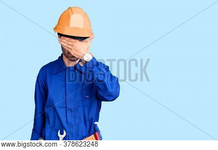 Young hispanic man wearing worker uniform covering eyes with hand, looking serious and sad. sightless, hiding and rejection concept