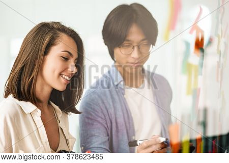 Image of multinational pleased colleagues smiling and using marker pen while working in office