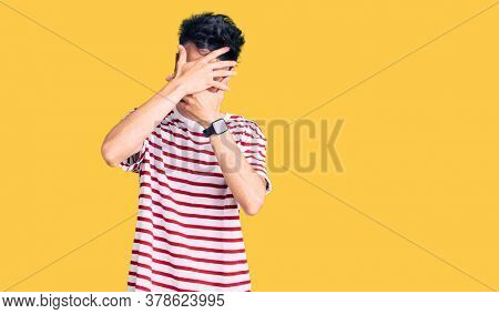 Young hispanic man wearing casual clothes covering eyes and mouth with hands, surprised and shocked. hiding emotion