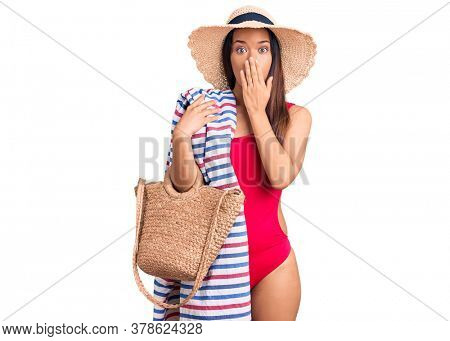 Young beautiful latin girl wearing swimwear and summer hat holding beach towel and bag covering mouth with hand, shocked and afraid for mistake. surprised expression