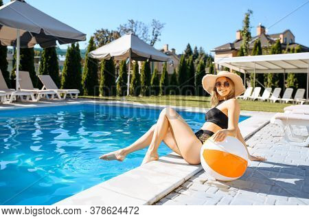 Slim woman with ball sitting at the poolside
