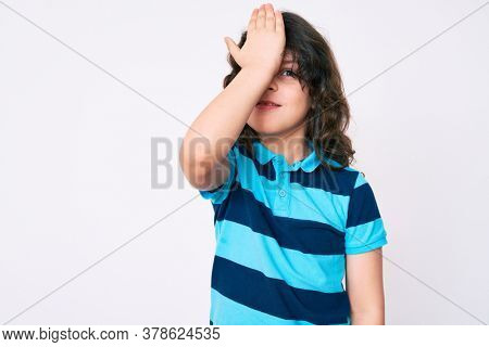 Cute hispanic child with long hair wearing casual clothes surprised with hand on head for mistake, remember error. forgot, bad memory concept.