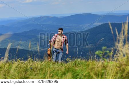 Carefree Wanderer. Vast Expanses. Peaceful Hiker. Conquer The Peaks. Man Hiker With Guitar Walking O