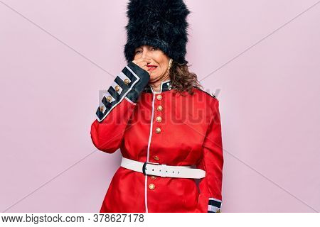 Middle age beautiful wales guard woman wearing traditional uniform over pink background smelling something stinky and disgusting, intolerable smell, holding breath with fingers on nose. Bad smell