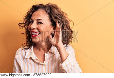 Middle age beautiful brunette woman wearing striped shirt standing over yellow background smiling with hand over ear listening and hearing to rumor or gossip. Deafness concept.