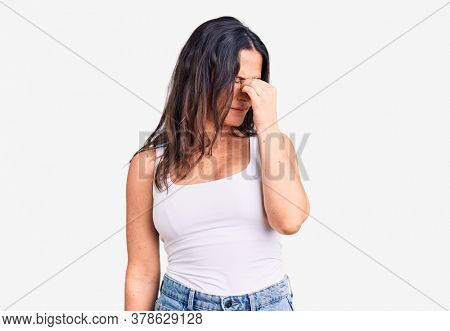 Young beautiful brunette woman wearing casual sleeveless t-shirt tired rubbing nose and eyes feeling fatigue and headache. stress and frustration concept.