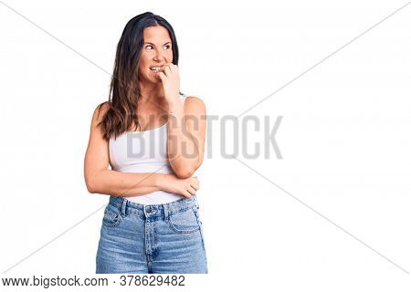 Young beautiful brunette woman wearing casual sleeveless t-shirt looking stressed and nervous with hands on mouth biting nails. anxiety problem.