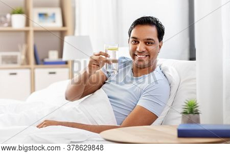 people, bedtime and rest concept - happy smiling indian man lying in bed at home and taking glass of water with lemon from table
