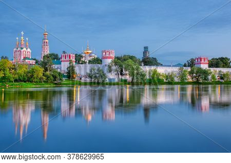 Novodevichy Monastery With A Reflection In The Lake At Sunset. The Famous Moscow Landmark With Golde