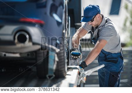 Caucasian Towing Company Worker Inn His 40s Securing Modern Vehicle On The Towing Truck Platform. Ca