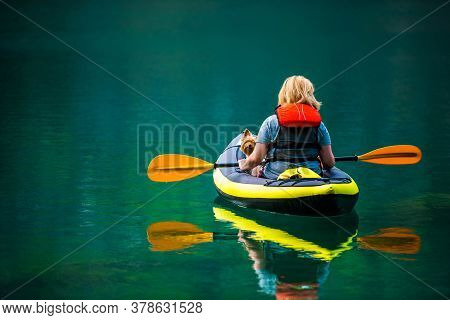 Caucasian Woman Kayaking With Her Australian Silky Terrier Dog During Summer Afternoon. Scenic Turqu