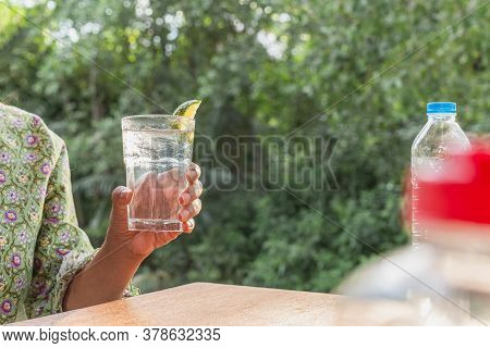 Woman Hand Holding Glass Of Water With Slice Of Lime.