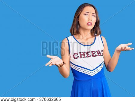 Young beautiful chinese girl wearing cheerleader uniform clueless and confused with open arms, no idea concept.