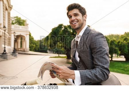 Image of a handsome happy cheery business man outdoors in park holding newspaper while looking aside
