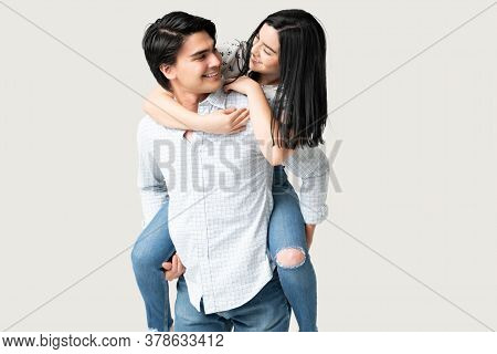 Happy Woman Piggyback Riding On Her Boyfriend Isolated Over White Background