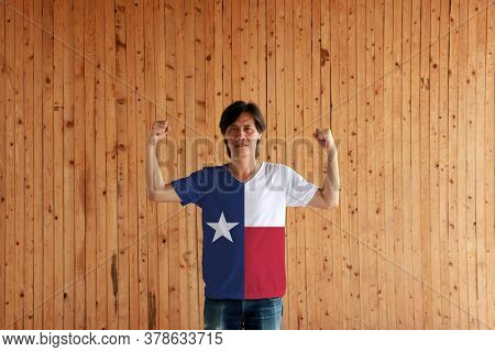 Man Wearing Texas Color Of Shirt And Standing With Raised Both Fist On The Wooden Wall Background. T