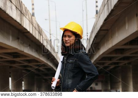 Female Civil Engineer Or Architect With Yellow Helmet, Standing With Project Drafts While In Hand On