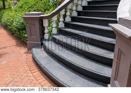 Sweeping Exterior Staircase With Black Cast Iron Treads Leading To A Brick Sidewalk In A Herringbone