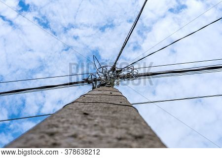 An Electric Pole With Wires Rising Up Towards A Blue Sky With Clouds. At The Top Of The Pole, Electr
