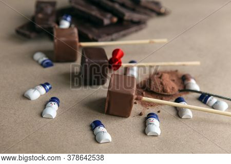 Small Snowmans Near Chocolate Cubes On A Stick With Aromatic Cocoa Powder And Chocolate On Brown Bac