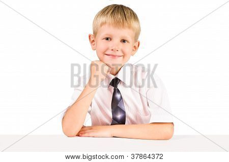 Portarat Of Smiling  Elementary Schoolboy While Sitting At A Table Isolated Over White