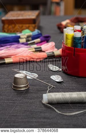 The Sewing Items Are On The Table. The Thread Is Threaded Over The Needle On The Thimble.