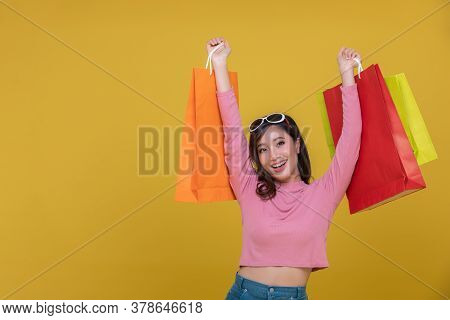 Portrait Asian Beautiful Happy Young Woman Smiling Cheerful And Holding Shopping Bags Isolated On Ye
